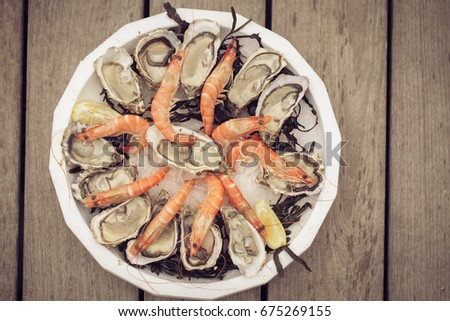 Fresh opened oysters on ta plate with shrimps and ice. Luxary food plate on the wooden background toned with soft old fashioned sepia colors. Concept of luxury, meal, bourgua, french style #675269155