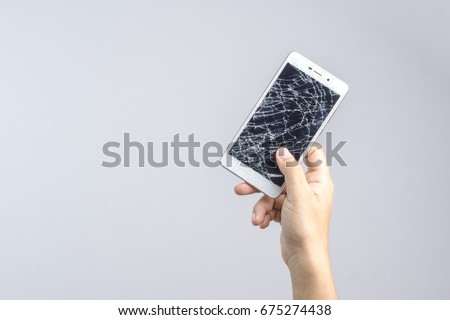 Hand holding mobile phone with broken screen on white background