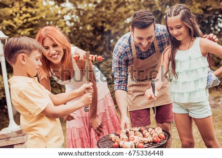 Happy family having a barbecue in their garden in summer.Leisure, food, family and holidays concept. #675336448