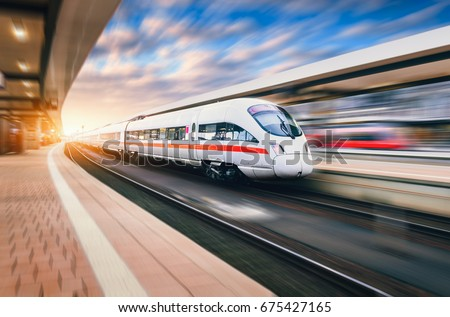 White modern high speed train in motion on railway station at sunset. Train on railroad track with motion blur effect in Europe in evening. Railway platform. Industrial landscape. Railway tourism #675427165