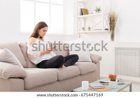 Young woman using smartphone at home on the couch. Dark-haired girl in casual texting online #675447169