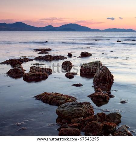 colorful sunrise on the rocky coast of sea #67545295