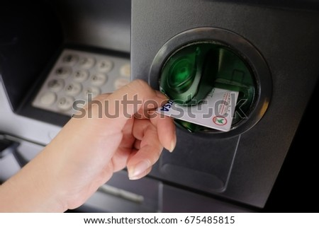 Bangkok, Thailand - July 11, 2017 : Close up of woman's hand inserting debit card into ATM machine to withdraw some money. #675485815