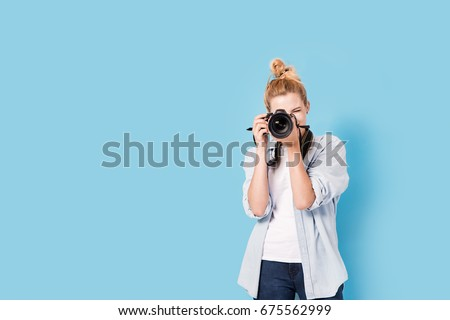Young blonde photographer is taking a photo. Model isolated on a blue background with copy space Royalty-Free Stock Photo #675562999