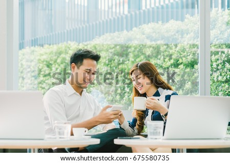 Young Asian couple, coworkers, or business partners have fun using smartphone together, with laptop computer at coffee shop. Information technology, cafe lifestyle, or romantic relationship concept #675580735