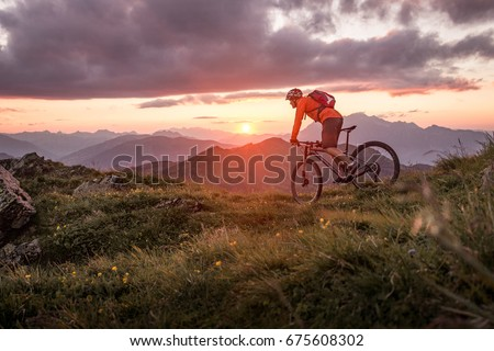 Male mountainbiker at sunset in the mountains Royalty-Free Stock Photo #675608302