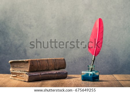 Vintage red quill pen with inkwell and old books on wooden table front concrete wall background. Retro instagram style filtered photo #675649255