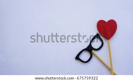 Top or flat lay view of Photo booth props a black spectacles and a red heart shape on a white background flat lay. Birthday parties and weddings. #675759322