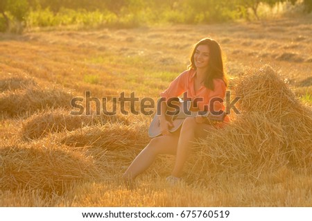 Happy cheerful girl playing guitar at hay bale at sunset. Young woman with guitar in the field #675760519