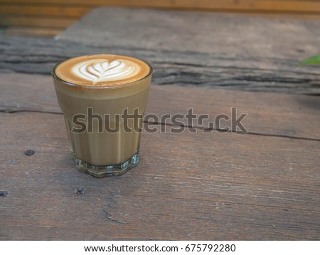 A cup of coffee with heart latte art on top on wood board.Vintage latte art coffee. #675792280