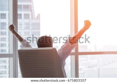 Business achievement concept with happy  businessman relaxing at work in office room, resting and raising fists with ambition success looking forward to city building urban scene through glass window Royalty-Free Stock Photo #675803107