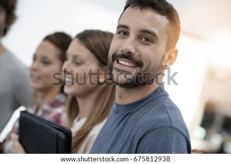 Portrait of cheerful guy in office with workmates #675812938