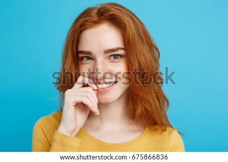 Headshot Portrait of happy ginger red hair girl with freckles smiling looking at camera. Pastel blue background. Copy Space. #675866836
