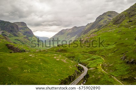 The Highlands, Scotland. Elevated drone image of a road running deep into the Grampian Mountains of the Scottish Highlands. #675902890
