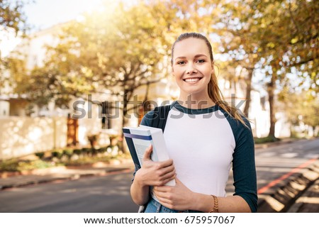 Young caucasian college student with book in college campus. University student going to college. #675957067