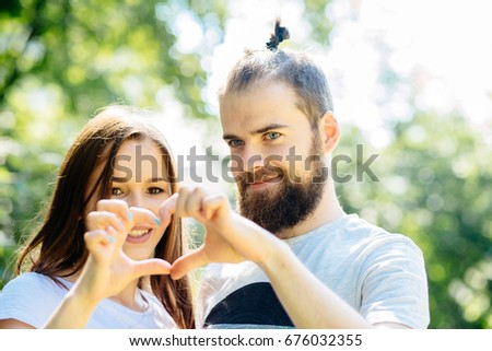 Love is in the air. Beautiful young hipster couple standing close to each other and looking through a heart shape made with their fingers #676032355