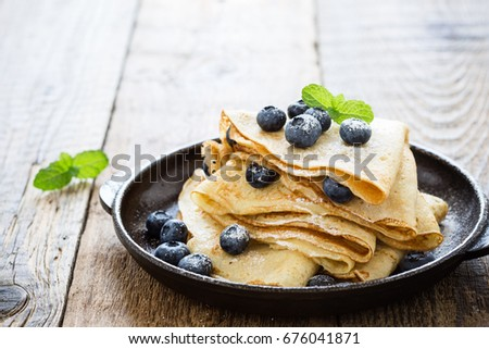 Homemade  crepes served with fresh blueberries and powdered sugar on rustic wooden table in cast iron skillet Royalty-Free Stock Photo #676041871