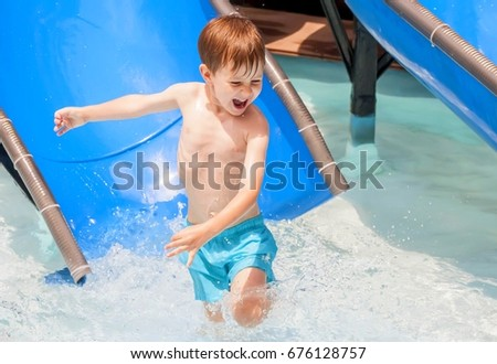 Happy Caucasian child enjoying the summer heat in the water park.