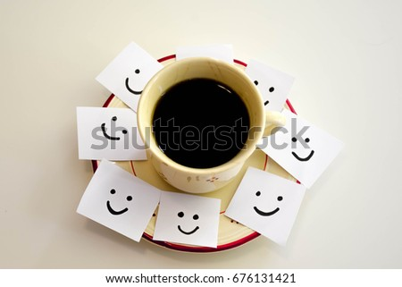 Cup of coffee and smiley faces on a white notes #676131421