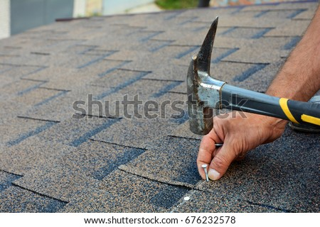 Worker hands installing bitumen roof shingles with hammer and nails. #676232578