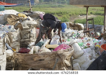 KOTA KINABALU, MALAYSIA - 09 JULY, 2017: Unidentified man collecting plastic bottle and unused item for recycle and resell at dumping site landfill at Kota Kinabalu,Sabah.Borneo. #676256818