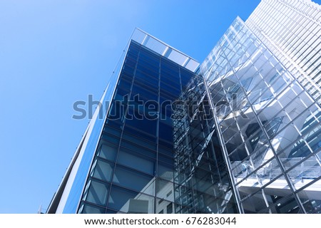 low angle view of office building with glass wall under blue sky #676283044