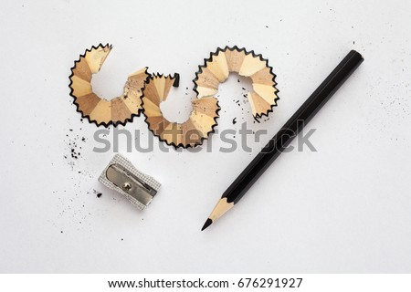 black wooden pencil, sharpener and pencil shavings on white paper Royalty-Free Stock Photo #676291927