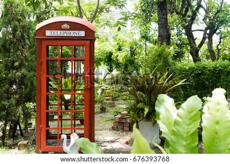 Red telephone booth in the garden. #676393768
