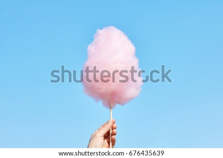 The hands of women holding pink cotton candy in the background of the blue sky Royalty-Free Stock Photo #676435639