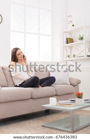 Happy girl talking on mobile phone sitting on the couch at home, copy space on window #676436383