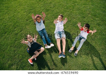 High angle view of cheerful multiethnic kids waving at camera with hands while resting on green meadow #676519690