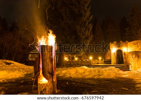 Massive wooden log on fire, with sparks, at fire camp in the mountains; night time  #676597942