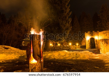 Massive wooden log on fire, with sparks, at fire camp in the mountains; night time  #676597954