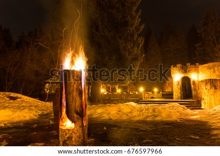 Massive wooden log on fire, with sparks, at fire camp in the mountains; night time  #676597966