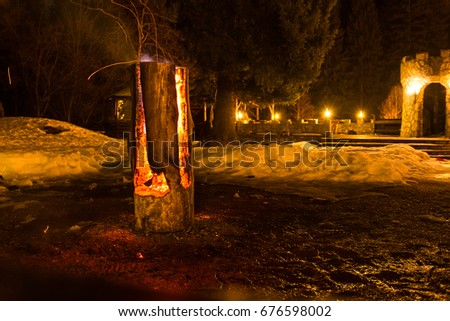 Massive wooden log on fire, with sparks, at fire camp in the mountains; night time  #676598002