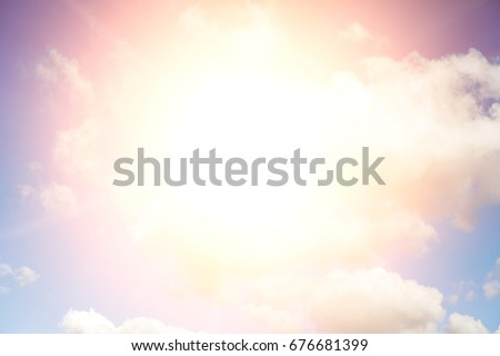 Bright sun with rays against a blue sky with white clouds