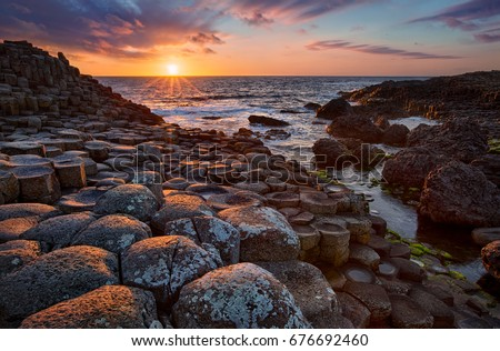 sunset over basalt columns Giant's Causeway known as UNESCO World Heritage Site, County Antrim, Northern Ireland Royalty-Free Stock Photo #676692460