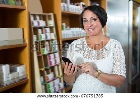 Young woman texting using her phone in healthy food store  #676751785