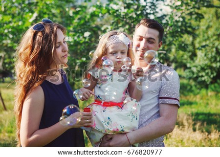 Little girl with parents playing in the Park, blowing bubbles. Happy family laughing. #676820977
