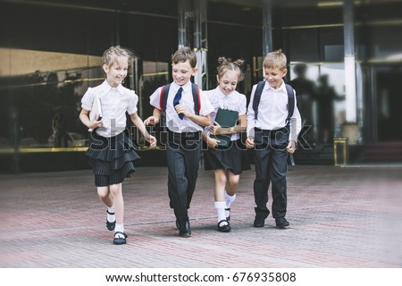 Beautiful school children active and happy on the background of school in uniform Royalty-Free Stock Photo #676935808