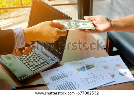 Business man working in coffee shop with his laptop and mobile smart phone gives money to business partner #677082532