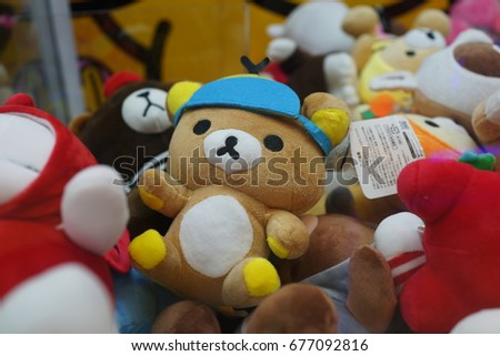 Close up of Japanese claw crane game machine soft toys and cuddly bears at the game centre #677092816