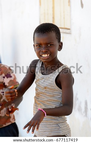 BUBAQUE, GUINEA BISSAU - MAY 5, 2017: Unidentified local little boy smiles in a village of the Bubaque island. People in G.-Bissau still suffer of poverty #677117419