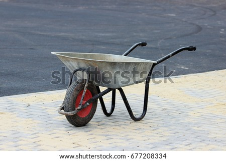 A construction empty wheelbarrow stands on the sidewalk next to an asphalt parking lot for tourist buses during construction. #677208334