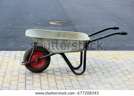 A construction empty wheelbarrow stands on the sidewalk next to an asphalt parking lot for tourist buses during construction. #677208343
