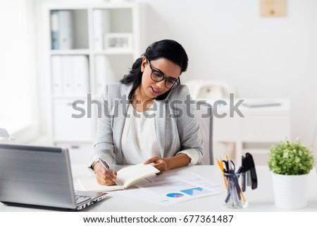 business, technology, communication and people concept - happy businesswoman or secretary with notebook calling on smartphone at office