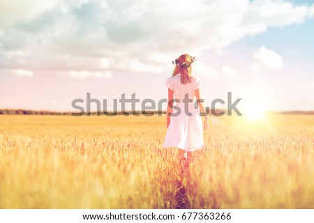 happiness, nature, summer holidays, vacation and people concept - smiling young woman in wreath of flowers and white dress walking along cereal field #677363266