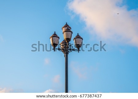 The old retro lamp post and the beautiful white and blue sky. #677387437
