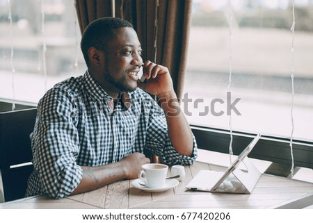 handsome man sit in cafe with computer and phone #677420206