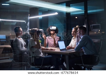 Multiethnic Business team using virtual reality headset in night office meeting  Developers meeting with virtual reality simulator around table in creative office. #677678614